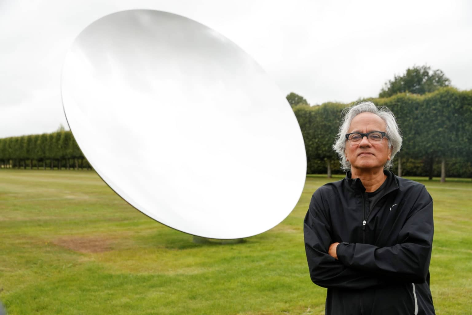 British-Indian artist Anish Kapoor poses with his sculpture in the gardens at Houghton Hall in Norfolk